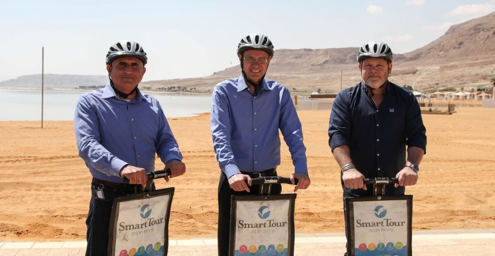From left to right, Shimon Daniel, the CEO of the Dead Sea Preservation Government Company Ltd, which oversaw the development of the new promenade and infrastructure, Tourism Minister Yariv Levin, and Tamar Regional Council Mayor Dov Litvinoff ride segways on the new promenade in Ein Boqek on April 3, 2017. (courtesy Mickey Lengental)