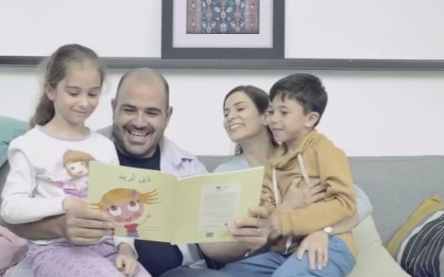An Israeli-Arab family reads together from a children's book (Maktabat al-Fanoos promotional video, YouTube)