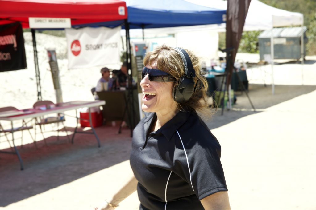 A woman with protective gear for her eyes and ears enjoying herself at Bullets & Bagels. (Courtesy)