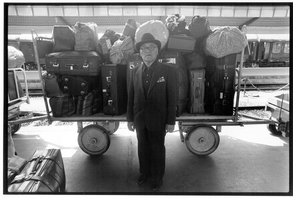 An elderly man stands in front of a luggage cart. (Courtesy 'Stateless')