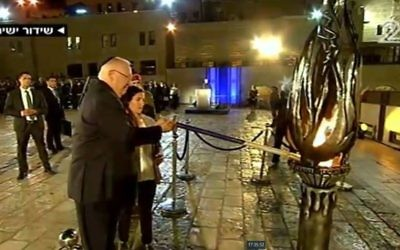 President Reuven Rivlin lights the memorial flame on together with the widow of a fallen IDF soldier Hagi Ben Ari at the official Memorial Day ceremony at the Western Wall in Jerusalem on April 30, 2017. (screen capture: Channel 2)