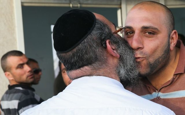 Illustrative image of an ultra-Orthodox Israeli contractor greeting a Palestinian construction worker as he and others wait on the Palestinian side of the checkpoint at the entrance to the West Bank settlement of Beitar Illit. (Nati Shohat/Flash90)