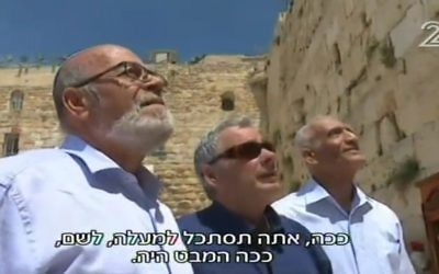 From L to R, Haim Oshri, Dr. Itzik Yifat and Zion Karasenti stand in front of the Western Wall in April 2017, 50 years after the three former paratroopers were resonantly photographed at the holy site by David Rubinger immediately after its capture in the Six Day War. (screen capture: Channel 2)