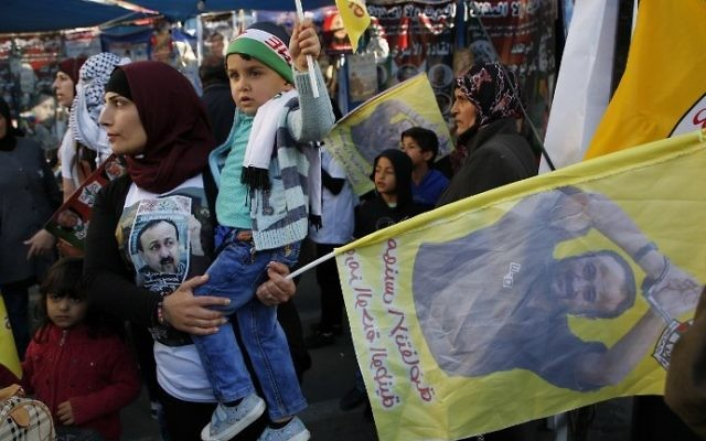 Palestinians hold flags bearing portraits of convicted Palestinian terrorist Marwan Barghouti during a rally in the West Bank city of Ramallah in support of prisoners on hunger strike on April 24, 2017. (AFP Photo/Abbas Momani)