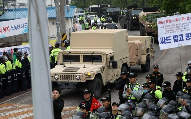 Protesters and police stand by as trailers carrying US THAAD missile defence equipment enter a deployment site in Seongju, South Korea, early on April 26, 2017. (AFP/Yonhap)