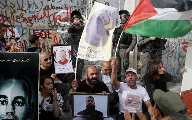 Palestinians protest in solidarity with security prisoners on a hunger strike by the security barrier in the West Bank city of Bethlehem on April 26, 2017. (AFP Photo/Musa Al Shaer)