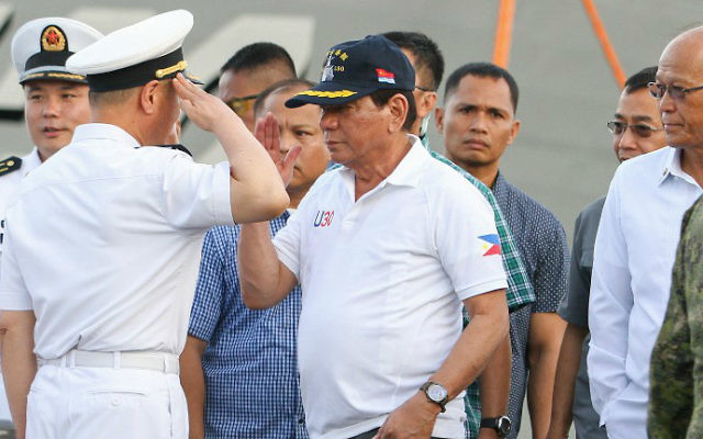 Philippine President Rodrigo Duterte (C) returns a salute from a Chinese naval officer (L) as Philippine Defense Secretary Delfin Lorenzana (R) looks on during Duterte's arrival to visit the guided missile frigate Changchun berthed at the Davao international port on May 1, 2017. (MANMAN DEJETO / AFP)