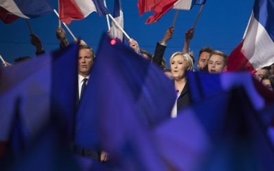 The French National Front's Marine Le Pen (R) and former French presidential election candidate for the right-wing Debout la France (DLF) party Nicolas Dupont-Aignan (L), sing the French National anthem at the end of a meeting at the Parc des Expositions in Villepinte, on May 1, 2017. (AFP/Joel Saget)