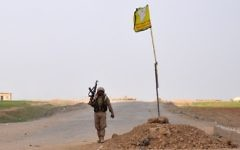 A fighter from the US-backed SDF walks next to the group's flag flying in the village of Kabsh Gharbi, on the northern outskirts of Raqqa, on May 2, 2017. (AFP Photo/Ayham al-Mohammad)