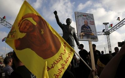 Protesters hold up portraits of Marwan Barghouti in front of a statue of Nelson Mandela in the West Bank city of Ramallah on May 3, 2017, during a demonstration in support of Palestinian prisoners on hunger strike in Israeli jails. (AFP/ABBAS MOMANI)