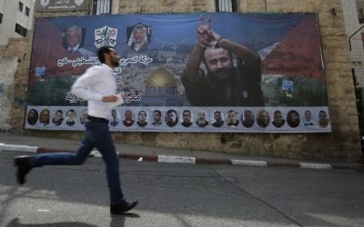 A Palestinian runs past a poster bearing a portrait of convicted terrorist and prominent Palestinian prisoner Marwan Barghouti in the West Bank city of Ramallah on May 3, 2017. (AFP/Abbas Momani)