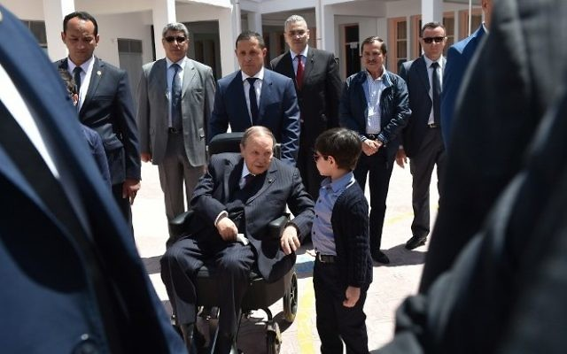 Algerian President Abdelaziz Bouteflika talks to his nephew after casting his vote at a polling station in Algiers on May 4, 2017 during parliamentary elections. (AFP / RYAD KRAMDI)