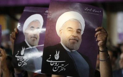 Supporters of Iranian President Hassan Rouhani hold his portrait during a campaign rally in the capital Tehran on May 4, 2017. (AFP Photo/Atta Kenare)