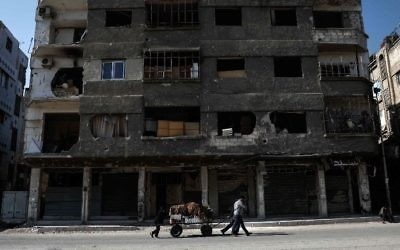 A Syrian street seller pulls a cart of vegetables past a destroyed building in the rebel-held town of Douma, on the eastern outskirts of Damascus on May 6, 2017. (Sameer Al-Doumy/AFP)