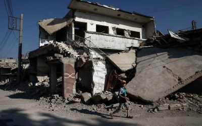 A Syrian boy walks past destroyed buildings in the rebel-held town of Douma, on the eastern outskirts of Damascus on May 6, 2017. (Sameer Al-Doumy/AFP)