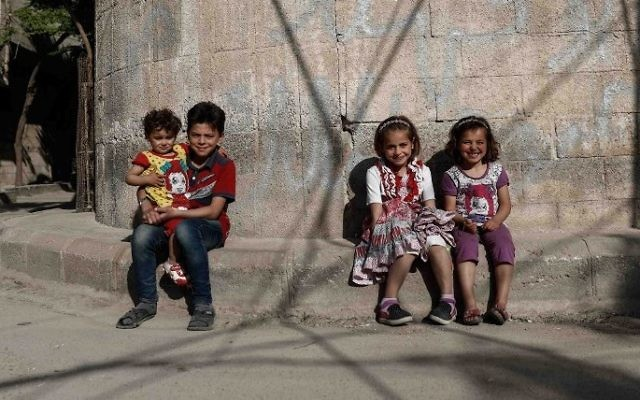 Syrian children pose for a photo near their house in the rebel-held town of Douma, on the eastern outskirts of Damascus on May 6, 2017. (Sameer Al-Doumy/AFP)