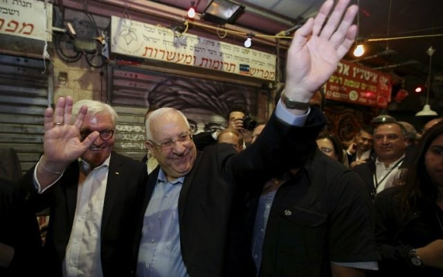 President Reuven Rivlin and his German counterpart  Frank-Walter Steinmeier wave as they visit the trendy outdoor Mahane Yehuda Market at night on May 6, 2017 in Jerusalem. (AFP Photo/Gali Tibbon)