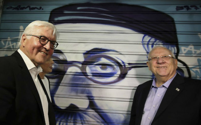 President Reuven Rivlin, right, and his German counterpart Frank-Walter Steinmeier, left, stand next to graffiti depicting Rivlin's great-grandfather as they visit the trendy outdoor Mahane Yehuda Market at night on May 6, 2017 in Jerusalem. (Gali Tibbon/AFP)