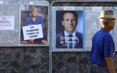 A man walks past election posters plastered close to a polling station in Saint-Leu, Reunion, on May 7, 2017, during the second round of the French presidential election. (AFP Photo/Richard Bouhet)