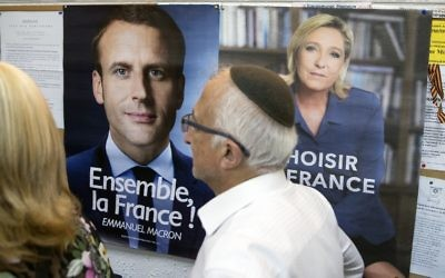 A French citizen residing in Israel walks past election posters of independent centrist French presidential candidate Emmanuel Macron (L) and far-right candidate Marine Le Pen, as he arrives to cast his vote at the French consulate in Tel Aviv, on May 7, 2017 during the second round of the French presidential polls. (AFP/ JACK GUEZ)