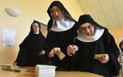 Benedictine Sisters of the Sainte-Cecile Abbey choose ballots before voting at a polling station in Solesmes, northwest France, May 7, 2017. (AFP/JEAN-FRANCOIS MONIER)