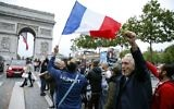 A man waves a French national flags next to people gesturing and shout on the French avenue of the Champs Elysees by the Arc de Triomphe on May 7, 2017, in Paris following the announcement of the results of the second round of the French presidential election. (AFP/ GEOFFROY VAN DER HASSELT)