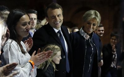 French president-elect Emmanuel Macron (C) and his wife Brigitte Trogneux (R) greet supporters in front of the Pyramid at the Louvre Museum in Paris on May 7, 2017, after the second round of the French presidential election. (AFP PHOTO / POOL / Thomas SAMSON)