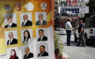 Palestinians stand near campaign posters displaying electoral lists ahead of municipal elections in the West Bank city of Bethlehem on May 10, 2017. (AFP/Thomas Coex)