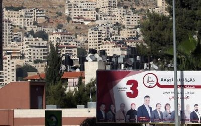 A picture taken on May 10, 2017 in the northern West Bank city of Nablus shows a campaign billboard displaying an electoral list ahead of municipal elections. (AFP/Jaafar Ashtiyeh)