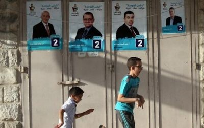 Children play past campaign posters displaying an electoral list ahead of municipal elections in the northern West Bank city of Nablus, on May 10, 2017 (AFP/Jaafar Ashtiyeh)