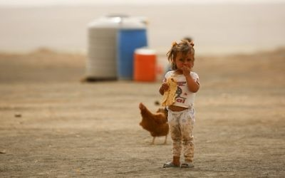 Illustrative image of a displaced child, who fled from the Islamic State (IS) group bastion of Raqqa, standing outside as she eats a loaf of bread in a camp for displaced near the town of al-Karamah on May 10, 2017. (AFP PHOTO / DELIL SOULEIMAN)