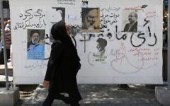 An Iranian woman walks past campaign posters on a commercial street in southern Tehran's Molavi neighborhood on May 11, 2017. (Atta Kenare/AFP)