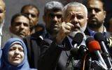Ismail Haniyeh, leader of the Hamas terror group, announces the arrest of the alleged killer of Hamas terror orchestrator Mazen Faqha, who was shot dead on March 24, 2017 near his home in Gaza City.  Faqha's wife is alongside Haniyeh. (AFP PHOTO / MOHAMMED ABED)