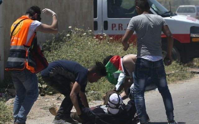 Palestinians tend to an injured demonstrator during clashes with Israeli forces in the West Bank village of Beit Furik, east of Nablus on May 12, 2017, after a demonstration following Friday prayers in solidarity with Palestinian prisoners on hunger strike in Israeli jails. (Jaafar Ashtiyeh/AFP)