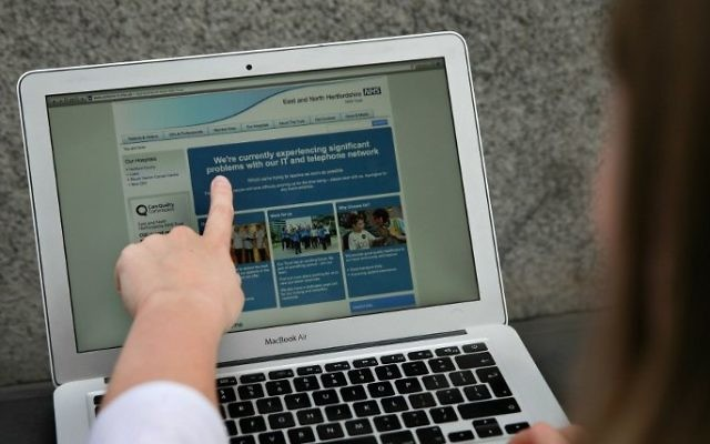 A woman points to the website of the NHS: East and North Hertfordshire notifying users of a problem in its network, in London on May 12, 2017. (AFP PHOTO / Daniel LEAL-OLIVAS)