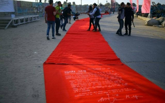 Palestinians walk on the red carpet, bearing the outline of the Balfour Declaration, during a film festival showcasing films focusing on human rights, in Gaza City on May 12, 2017. (AFP PHOTO / MOHAMMED ABED)