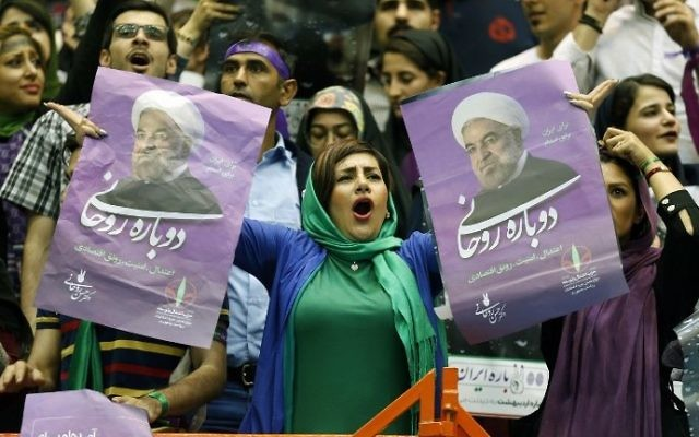 A supporter of Iranian President and presidential candidate Hassan Rouhani holds up his portrait during a campaign rally in the capital Tehran on May 13, 2017. (AFP PHOTO / ATTA KENARE)