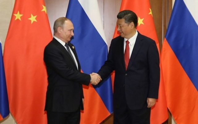 Russia's President Vladimir Putin (L) shakes hands with his Chinese counterpart Xi Jinping ahead of a bilateral meeting at Diaoyutai State Guesthouse in Beijing on May 14, 2017. (AFP Photo/Pool/Wu Hong)