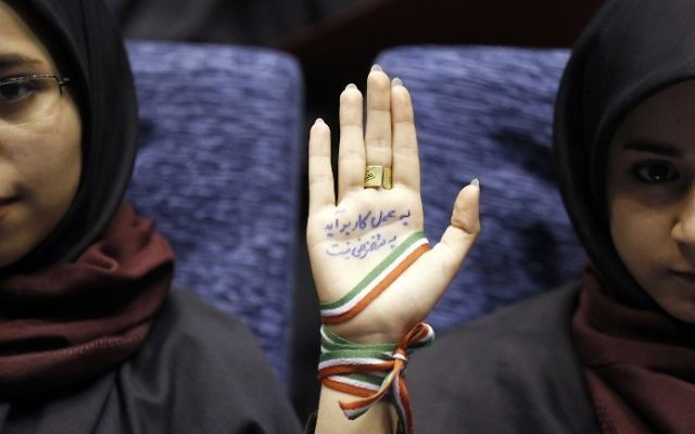 "A supporter of Iranian conservative presidential candidate and Tehran mayor Mohammad Bagher Ghalibaf attends a campaign rally in the Iranian capital Tehran on May 14, 2017, with her hand wrapped with a band carrying the colors of the Iranian national flag and ink on her palm reading in Persian: ""With action not by speech you can finish the job and work.""  (AFP PHOTO / ATTA KENARE)"