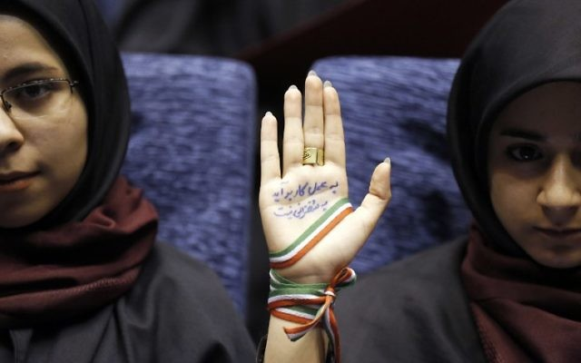 "A supporter of Iranian conservative presidential candidate and Tehran mayor Mohammad Bagher Ghalibaf attends a campaign rally in the Iranian capital Tehran on May 14, 2017, with her hand wrapped with a band carrying the colours of the Iranian national flag and ink on her palm reading in Persian: ""With action not by speech you can finish the job and work."" (AFP PHOTO / ATTA KENARE)"