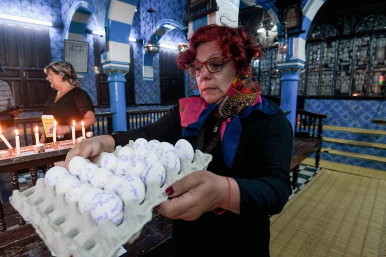A French Jewish woman carries a carton of eggs with her family's wishes written on them at the Ghriba Synagogue on the Tunisian resort island of Djerba on May 14, 2017 during the second day of the annual Jewish pilgrimage to the synagogue thought to be Africa's oldest. (AFP PHOTO / FETHI BELAID)