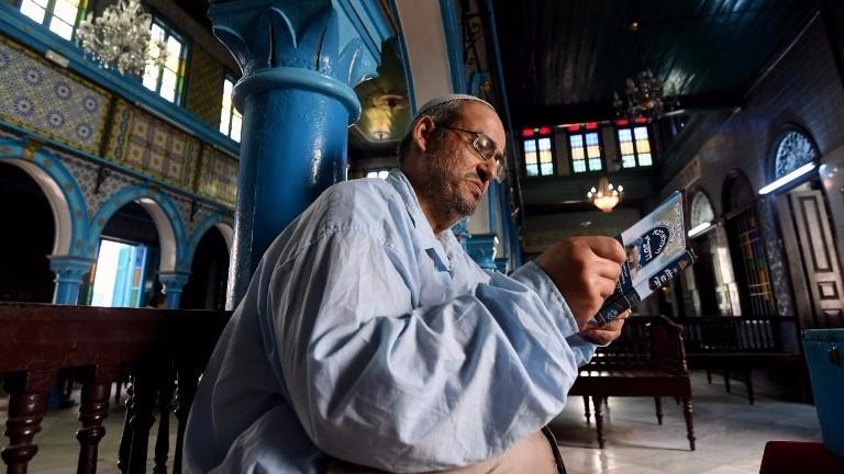 Tunisian Rabbi Daoud reads from a prayer book at the Ghriba Synagogue on  the Tunisian resort