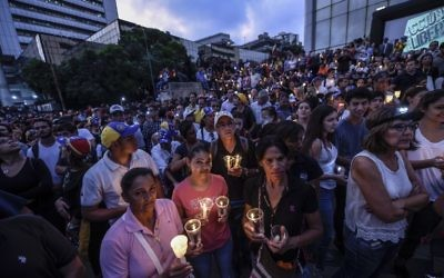 Opposition activists holding candles protest against the deaths of 43 people in clashes with the police during weeks of demonstrations against the government of Venezuelan President Nicolas Maduro, in Caracas on May 17, 2017.  (AFP JUAN BARRETO)