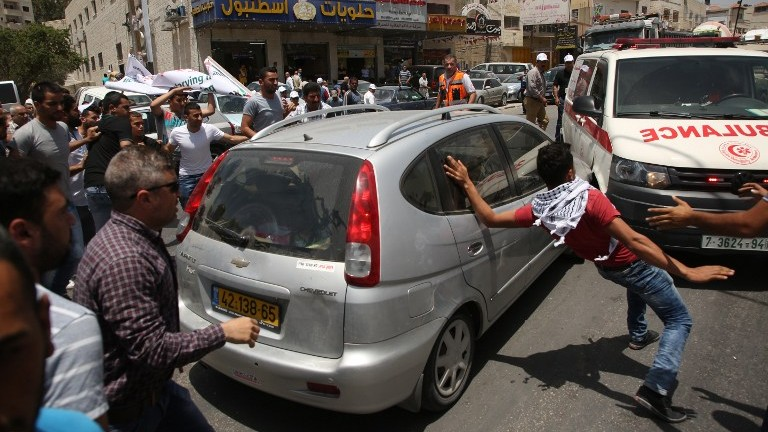 Palestinian protesters attack a car reportedly driven by an Israeli settler as it attempts to cross a crowd of demonstrators near the Hawara military checkpoint in the northern West Bank on May 18, 2017. (AFP Photo/Jaafar Ashtiyeh)