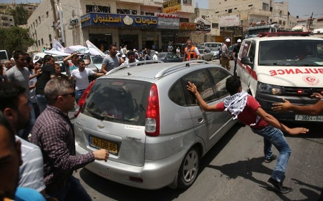 Palestinian protesters surround a car reportedly driven by an Israeli settler as it attempts to cross a crowd of demonstrators near the Hawara military checkpoint in the northern occupied West Bank on May 18, 2017.  A Palestinian was killed by an Israeli settler during a clash near the city of Nablus in the occupied West Bank, the Palestinian health ministry and security sources said. The clash near a military post erupted when an Israeli settler in a car attempted to cross a crowd of Palestinian protesters, with the settler and Israeli soldiers opening fire, Palestinian security sources said. / AFP PHOTO / JAAFAR ASHTIYEH