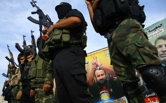 Members of terror groups in the Gaza Strip stand in front of a portrait of Marwan Barghouti as they attend a press conference in Gaza City in solidarity with Palestinian prisoners on hunger strike in Israeli jails on May 18, 2017. ( AFP PHOTO / MOHAMMED ABED)