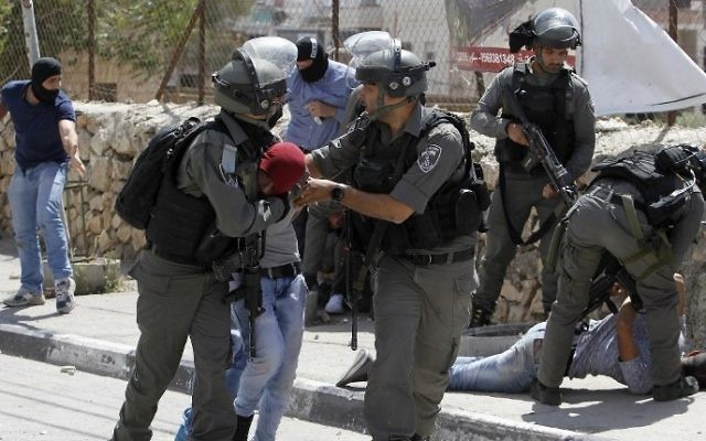 Israeli border guards and undercover police detain a Palestinian protester during clashes at the entrance of the West Bank city of Bethlehem on May 19, 2017. (AFP PHOTO / Musa AL SHAER)