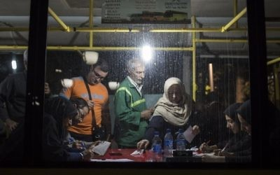 Iranians cast their vote inside a bus, used as a mobile polling station, during the presidential election in Tehran on May 19, 2017. (Behrouz Mehri/AFP)
