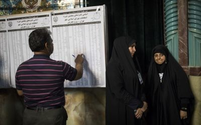 An Iranian man checks the list of municipal council elections ahead of voting at a polling station in Tehran on May 19, 2017. / AFP PHOTO / Behrouz MEHRI