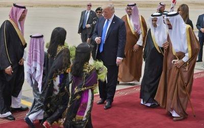 Children arrive with flowers for US President Donald Trump (C) during his welcoming by Saudi Arabia's King Salman bin Abdulaziz al-Saud (R), upon Trump's arrival at King Khalid International Airport in Riyadh on May 20, 2017. ( AFP PHOTO / MANDEL NGAN)